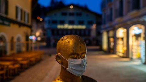 Eine Statue mit Mundschutz in der leeren Fußgängerzone von Berchtesgaden.