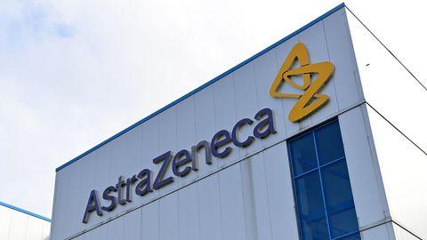 """An einer weißen Wellblech-Fabrikhalle hängt der Schriftzug """"AstraZeneca"""", daneben ein gelbes Logo aus stilisierten Buchstaben"""