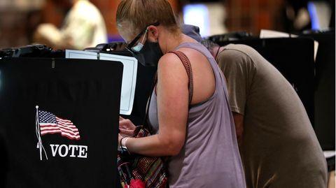 Wähler füllen in einer Wahlkabine ihre Stimmzettel aus