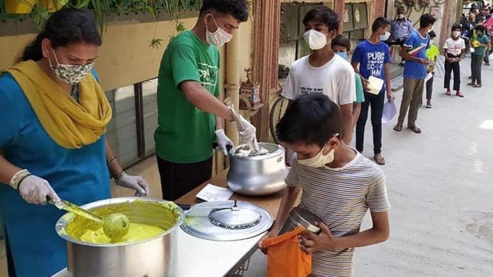"""Kinder stehen Schlange an der Essensausgabe des """"Sunshine Project"""" in Delhi"""