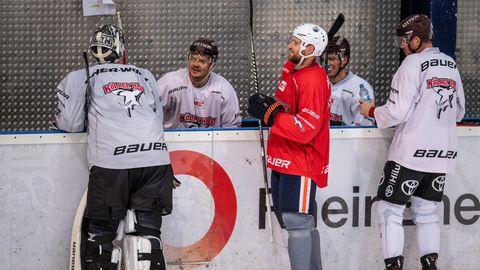 An der Bande eines Eisstadions stehen drei Eishockey-Profis in voller Montur. Zwei sitzen auf einer Bank hinter der Bande