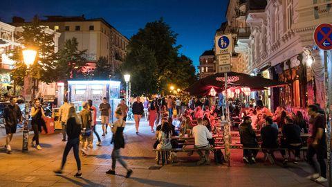 Auf einem breiten Fußweg sitzen zur blauen Stunde junge Menschen auf Bierbänken und trinken trotz Corona