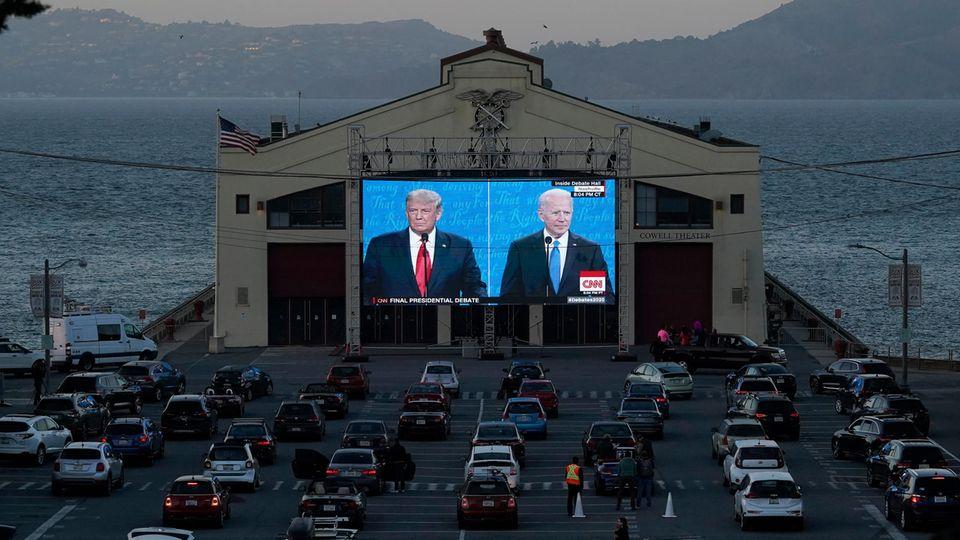Autos stehen vor eine Leinwand, auf der Trump und Biden gezeigt werden