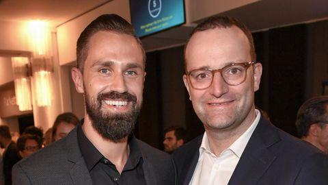 Zwei Männer in Anzügen stehen nebeneinander und lächeln. Der linke hat einen Vollbart, der rechte ist Brillenträger und rasiert