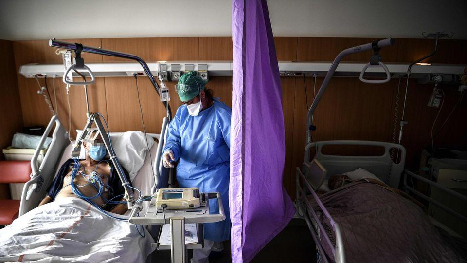 Ein Mann liegt mit Mund-Nasen-Schutz in einem Krankenhausbett. Eine Pflegekraft in blauer Schutzkleidung steht daneben