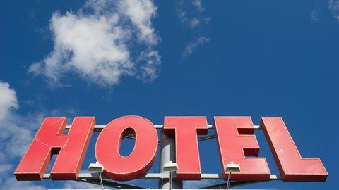 """Vor einem blauen Himmel mit nur einer Wolke ist ein rotes """"Hotel""""-Leuchtschild zu sehen"""