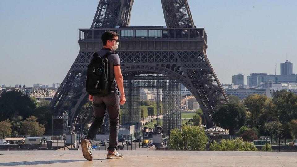 Ein Passant geht mit Mundschutzmaske über den Place du Trocadéro