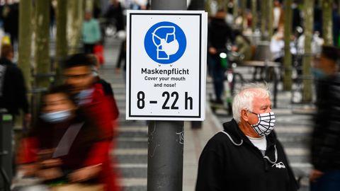 """Hessen, Frankfurt/Main: Ein Mann steht mit Maske neben einem Hinweisschild """"Maskenpflicht"""" auf der Einkaufsstraße Zeil."""
