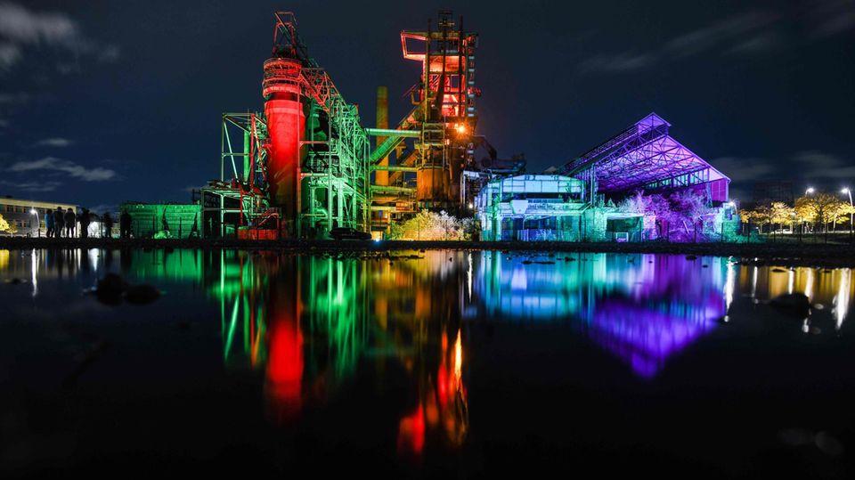 """Dortmund, Deutschland. Der Hochofen der Phoenix West erstrahlt in bunten Farben. Während der """"lichtkunst.ruhr""""werden zahlreiche Industriedenkmäler des Ruhrgebiets so und ähnlich illuminiert."""