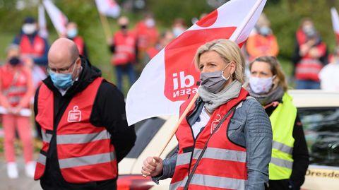 Sachsen, Dresden: Teilnehmer eines ganztägigen Warnstreiks stehen während einer Kundgebung auf dem Güntzplatz