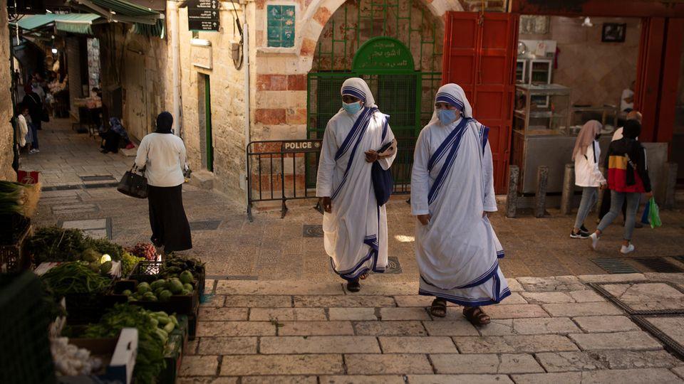Israel, Jerusalem: Katholische Nonnen gehen mit Mund-Nasen-Schutz über einen Platz in der Altstadt von Jerusalem
