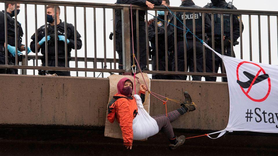Ein Aktivist hat sich von einer Brücke über die Autobahn 5 am Flughafen Frankfurt abgeseilt