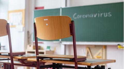 """""""Coronavirus"""" steht auf einer Tafel in einem leeren Klassenzimmer"""