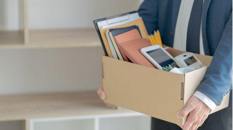Mann verlässt mit Kiste das Büro