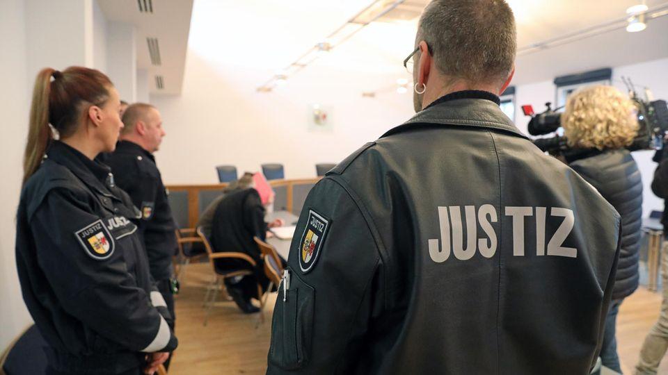 Justizvollzugsbeamte stehen im Saaldes Langerichts Neubrandenburg. Hier wurden ein Vater und sein Sohn am Montag zu mehrjährigen Haftstrafen verurteilt.