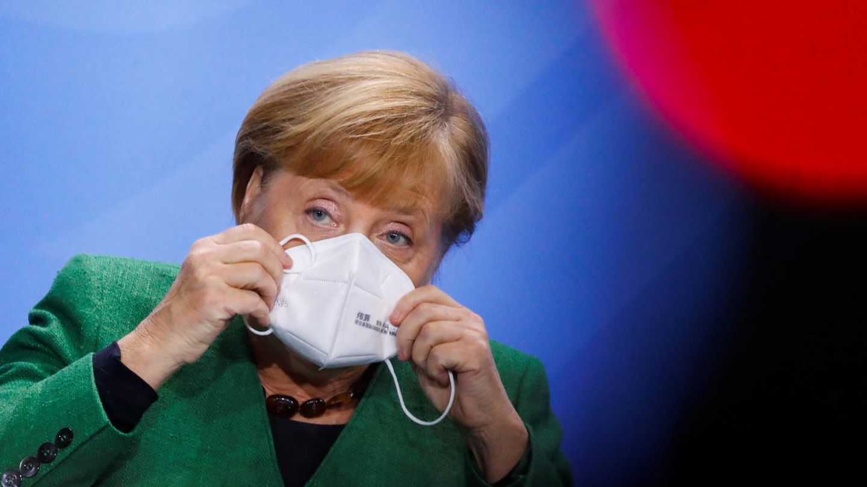 Angela Merkel setzt sich eine Maske auf