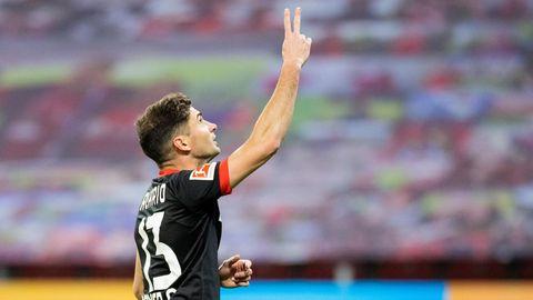 Ein Mann im schwarzen Fußballtrikot mit weißer Rückennummer 13 zeigt mit Zeige- und Mittelfinger der rechten Hand zum Himmel