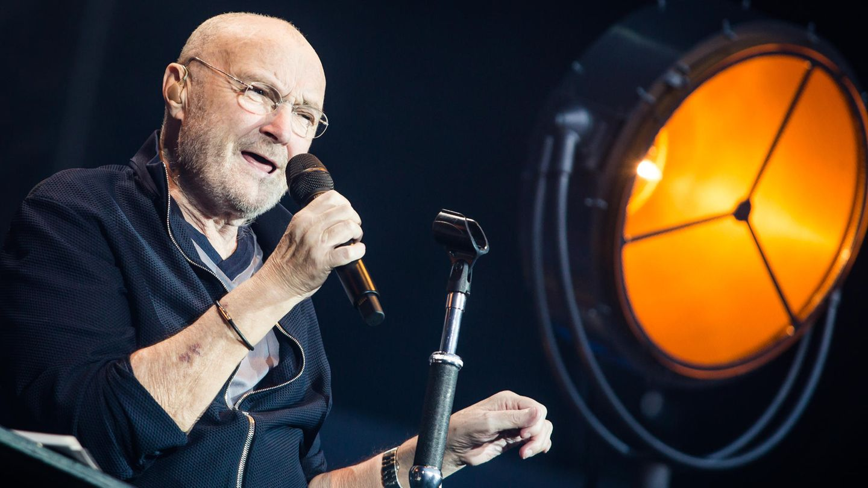 """2019 in Stuttgart: Sänger Phil Collins sitzt auf der Bühne und singt. Die britische Musiklegende will US-Präsident Trump untersagen, seinen Hit-Song """"In The Air Tonight"""" im Wahlkampf einzusetzen."""