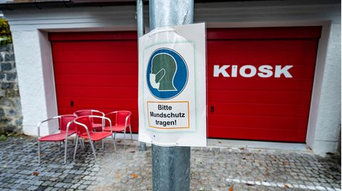 """Ein Hinweisschild mit der Aufschrift: """"Bitte Mundschutz tragen!"""""""