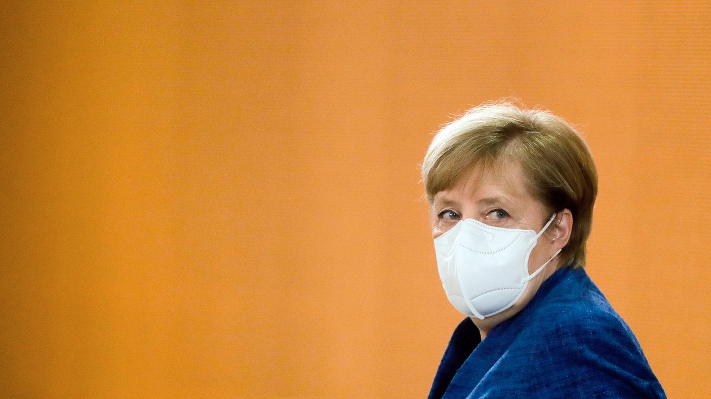 Bundeskanzlerin Angela Merkel trägt einen weißen Mund-Nasen-Schutz sowie ein blauen Blazer. Sie schaut über die linke Schulter