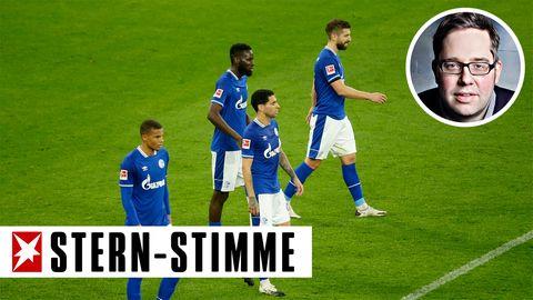 Vier Fußballspieler in blauen Schalke-Trikots gehen niedergeschlagen über den Platz