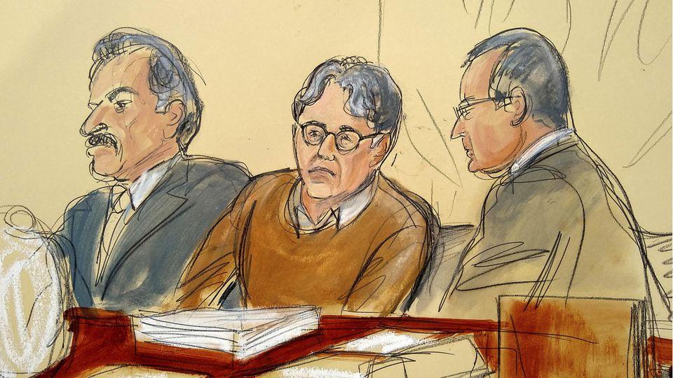 Ein Mann mit Brille und braunem Pullover sitzt zwischen zwei Anwälten in Anzügen