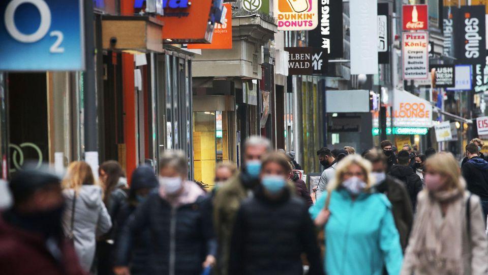 Nordrhein-Westfalen, Köln: Menschen gehen mit Schutzmasken durch die Fußgängerzone