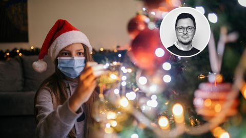 Ein Mädchen mit Maske schmückt den Weihnachtsbaum