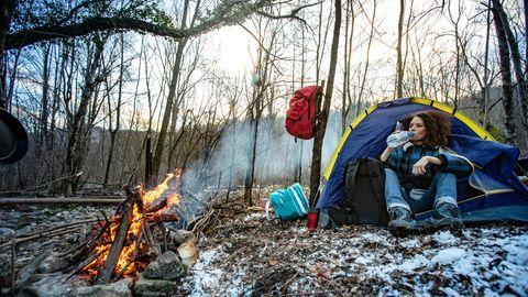 Eine Frau sitzt in ihrem Zelt im Wald