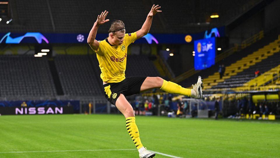 Im gelben BVB-Trikot und schwarzer Hose springt Erling Haaland mit ausgestreckten Armen und Beinen über den Rasen