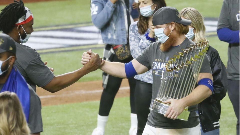 Justin Turner (rechts) von den Los Angeles Dodgers feiert nach dem Spiel mit der World-Series-Trophäe