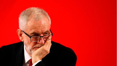 Vor einer roten Wand stützt ein grauhaariger Mann mit Vollbart und Brille seinen Kopf auf