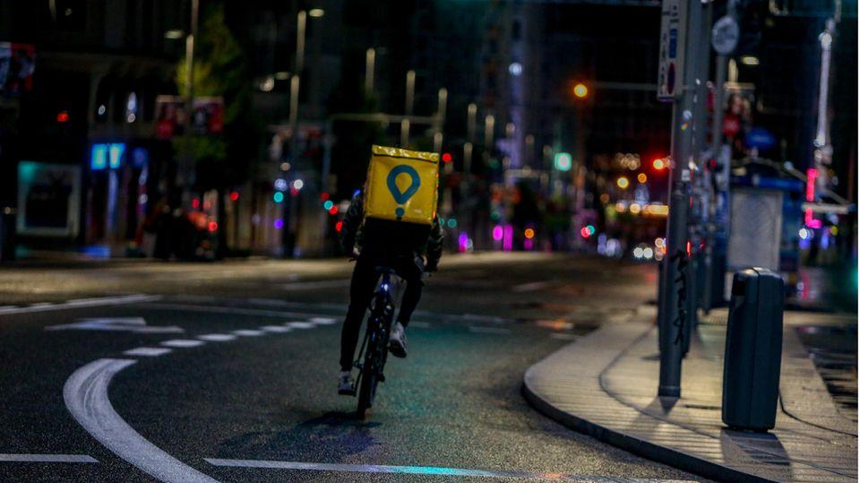 Einsamer Fahrradbote in den leeren Straßen von Madrid