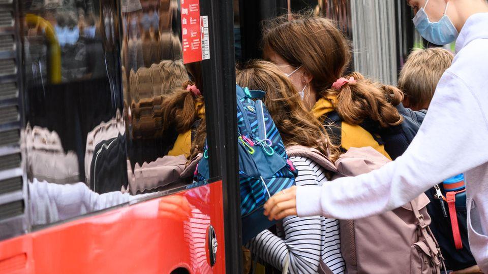 Kinder stürmen nach Schulende in einen Bus