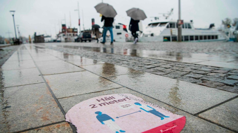 Ein Aufkleber im verregneten Stockholm weißt auf Abstandsregeln