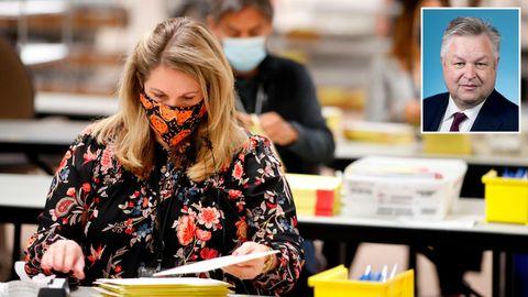 Eine blonde Frau mit Mundschutz und geblümter Bluse sitzt an einem Tisch und sortiert Briefwahl-Unterlagen
