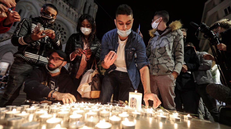 Menschen zünden Kerzen auf der Straße vor der Kirche Notre Dame für die Opfer einer Messerattacke an