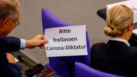 Ein AfD-Bundestagsabgeordneter zeigt Fraktionschefin Alice Weidel ein Blatt mit dem neuen Hauptthema der AfD