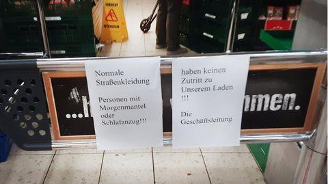 Papierschilder weisen auf ein Verbot von Schlafanzügen im Edeka-Markt hin