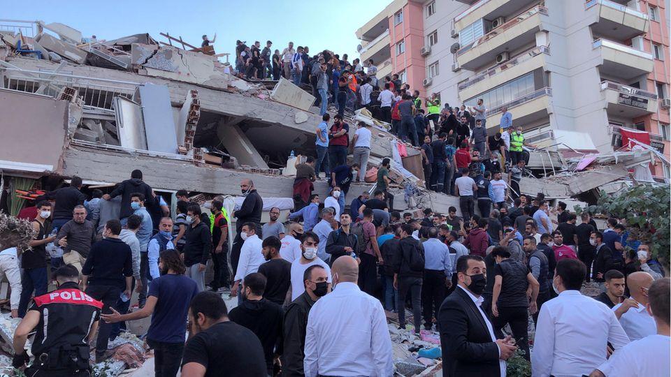 Menschen auf den Trümmern eines durch ein Erdbeben eingestürztes Haus in Izmir