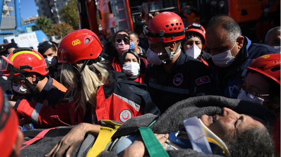 Auf einer Liege tragen Retter in roten Jacken und Helmen eine schwarzhaarige Frau über die Trümmer eines eingestürzten Gebäudes