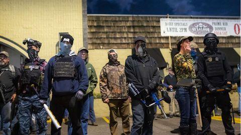 Auf einem Parkplatz steht eine Gruppe bewaffneter Menschen. Sie tragen teils schusssichere Westen und sind vermummt