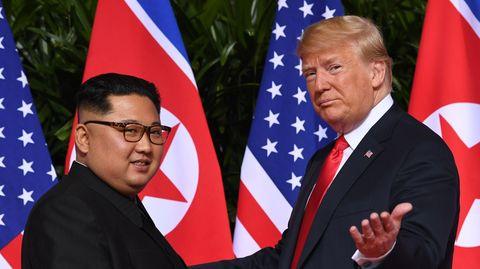 Vor den Flaggen der USA und Nordkoreas stehen Kim Jong Un links und Donald Trump rechts