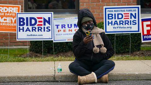Eine Frau sitzt mit ihrem Handy auf dem Bürgersteig, hinter ihr sind Schilder für Donald Trump oder Joe Biden.