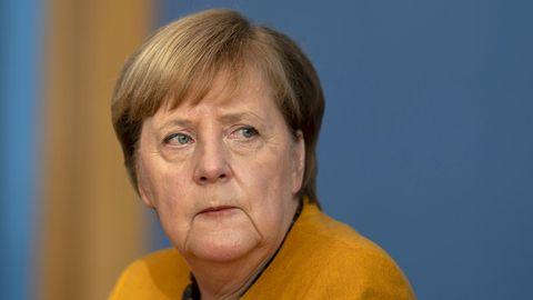 Bundeskanzlerin Angela Merkel im senfgelben Jacket schaut besorgt