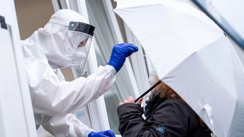 Eine Frau bekommt einen Rachenabstrich an einer Corona-Teststation