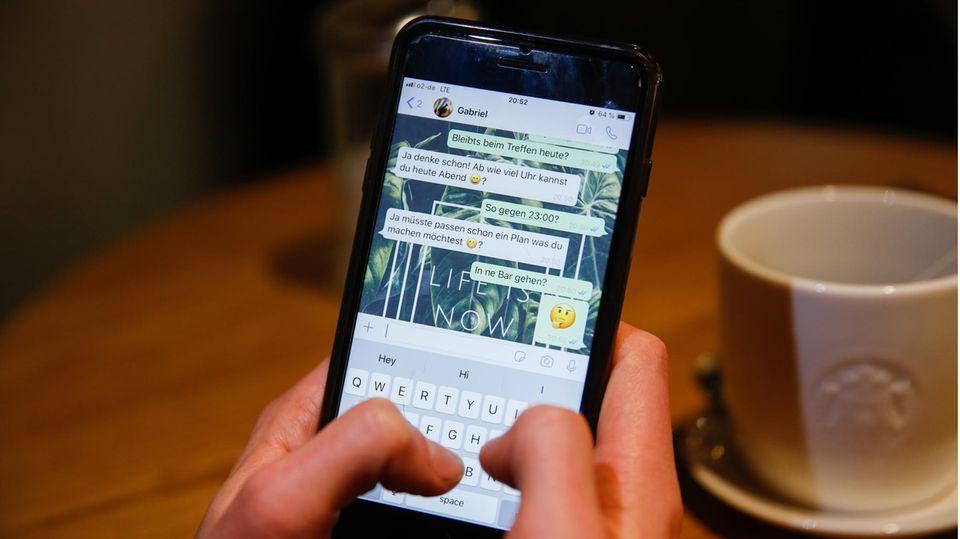 Ein junger Mann benutzt den Messengerdienst Whatsapp auf seinem Handy und schreibt.