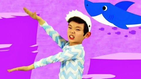 Ein Kind tanzt den Baby Shark-Tanz im Originalvideo, vor einem pinken Hintergrund