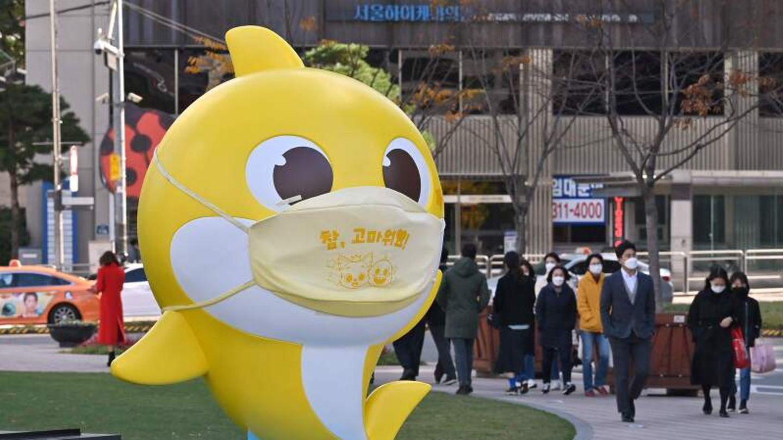 """Eine Statue eines gelben Haies """"Baby Shark"""" steht mit einem Mundschutz in einer Fußgängerzone."""