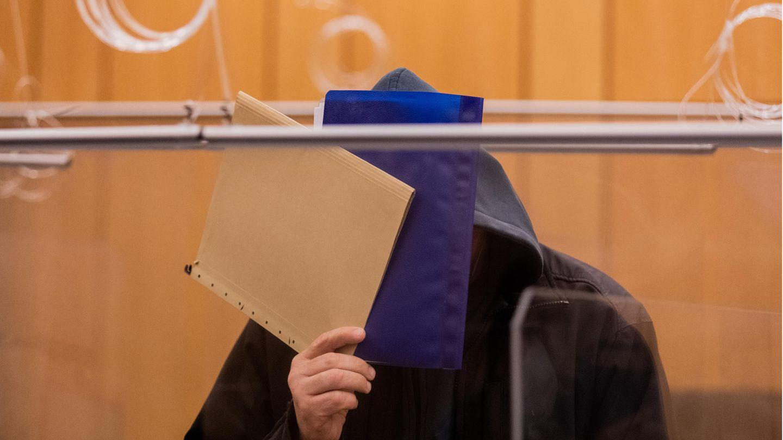 Der Angeklagte im Missbrauchsfall Münster verdeckte im Gerichtssaal im Landgerichtsein Gesicht